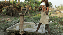 A young girl drinking from a water pump in Muzaffarpur India