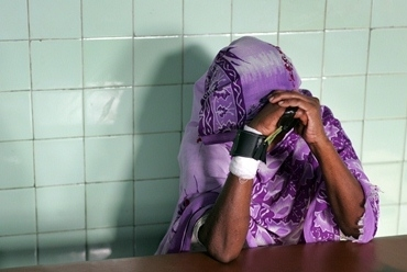 A woman with leprosy hides her face