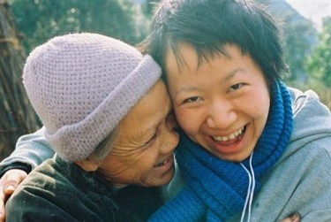 A volunteer laughs with a leprosy-affected woman in China
