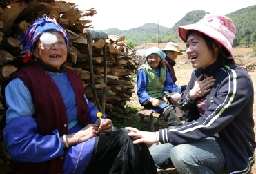 A leprosy-affected woman and a volunteer laugh together