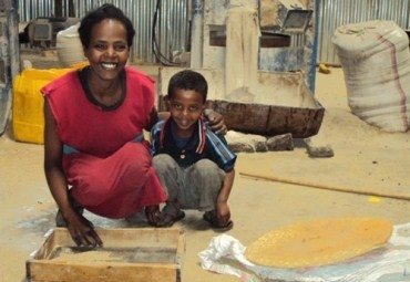 A woman with her son at a grain mill in Ethiopia