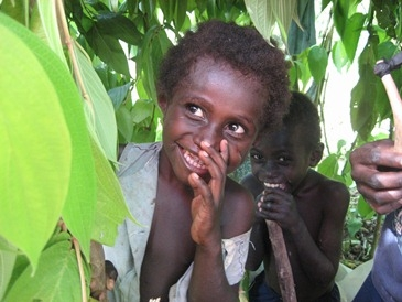 A Bougainville girl peeks out from the leaves
